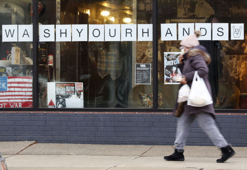 """In this March 19, 2020, photo, a woman in a face mask walks past a """"Wash Your Hands"""" sign after buying groceries in Oak Park, Ill., before a two-week """"shelter in place"""" order goes into effect. (Martha Irvine/AP)"""