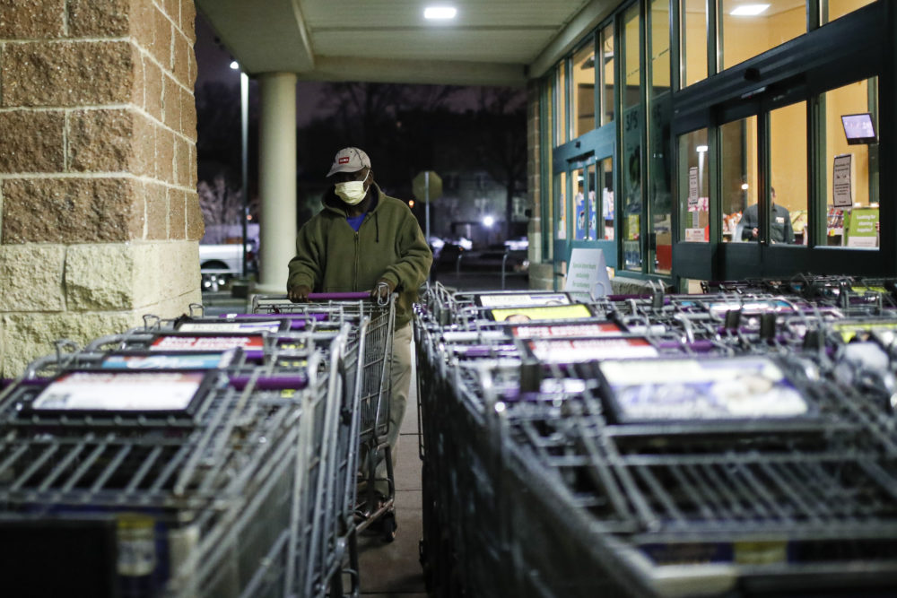 A customer wearing protective gloves and a face mask selects a cart outside a supermarket. (John Minchillo/AP)