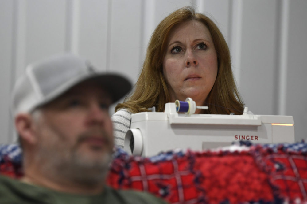 Jennifer Snead sitting in front of her sewing machine, and her husband Buddy Snead, both of Annapolis, Md., take a pause as they watch a news conference with Maryland Gov. Larry Hogan in their Annapolis home, Monday, March 23, 2020. (Susan Walsh/AP)