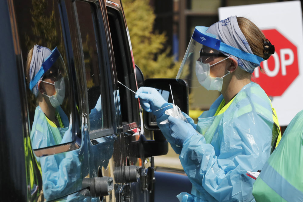 Healthcare workers test a person at a COVID-19 drive-thru testing site at Henry Ford West Bloomfield Hospital, Wednesday, March 25, 2020, in West Bloomfield, Mich. (Carlos Osorio/AP)