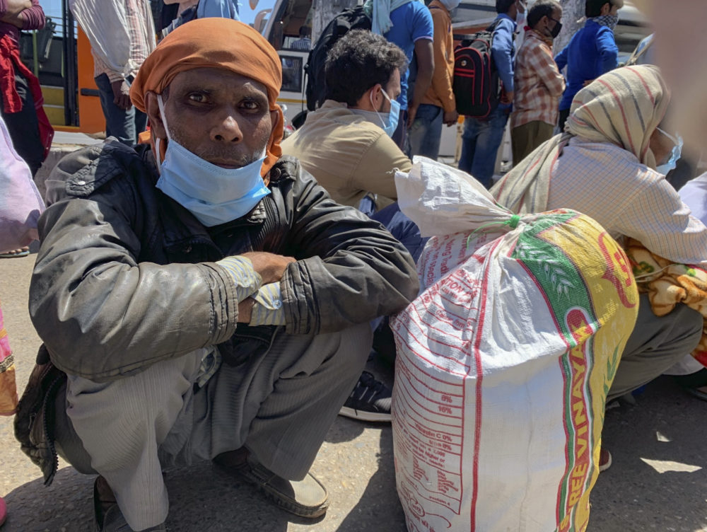 R.K. Sharma, 53, who is among hundreds waiting in line to cross a border to the neighboring state of Uttar Pradesh, in New Delhi, India, Sunday, March 29, 2020. (Emily Schmall/AP Photo)