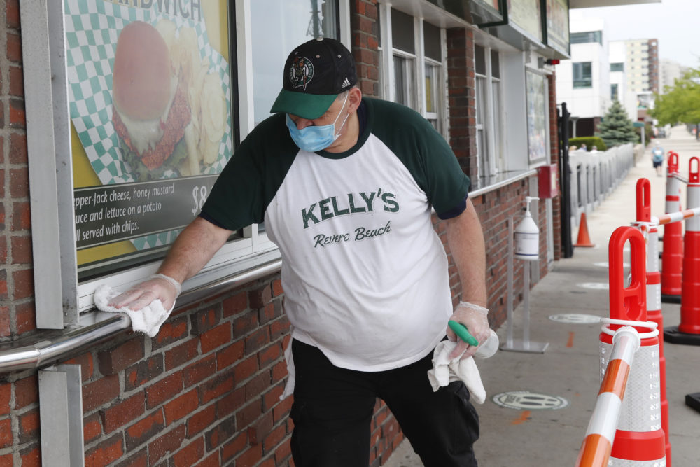 Chris Dotoli wipes down surfaces, June 3, 2020, outside Kelly's Roast Beef in Revere. Kelly's is open for outside delivery of food in accordance with the state's coronavirus guidelines. (Elise Amendola/AP)