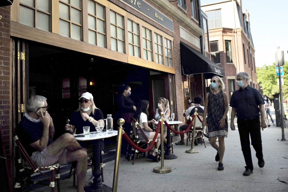 Passers-by, right, walk past diners at a cafe, June 25, 2020, in Boston. (Steven Senne/AP)