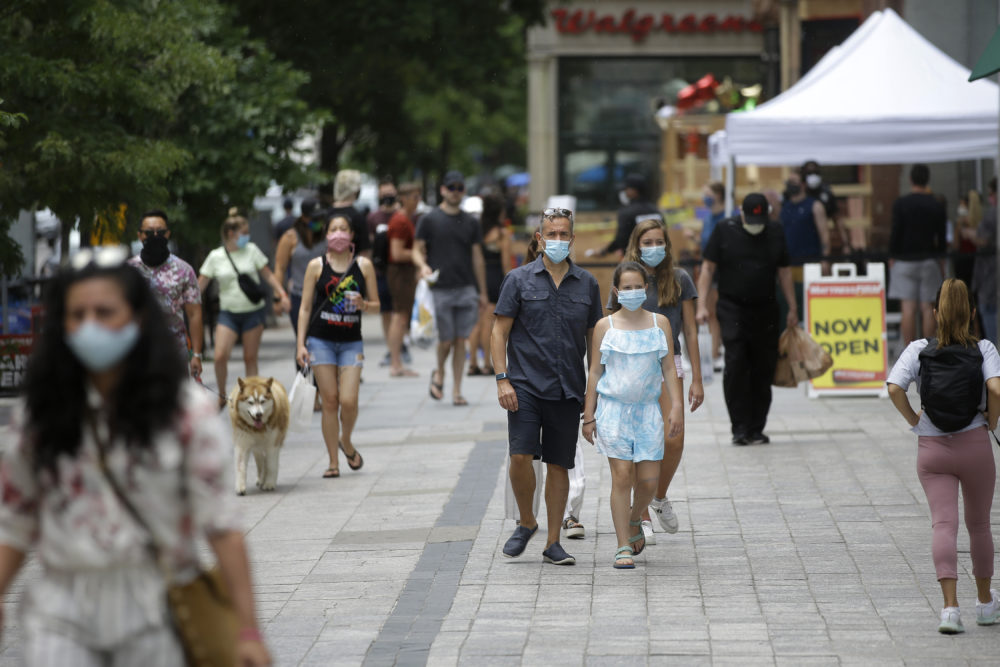 Pedestrians wear masks out of concern for the coronavirus, June 28, 2020, while walking along a sidewalk, in Boston.(Steven Senne/AP)