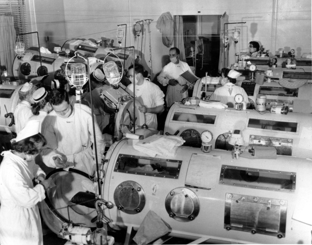 This is a scene in the emergency polio ward at Haynes Memorial Hospital in Boston, Ma., on Aug. 16, 1955. The city's polio epidemic hit a high of 480 cases. The critical patients are lined up close together in iron lung respirators so that a team of doctors and nurses can give fast emergency treatment as needed. (AP Photo)