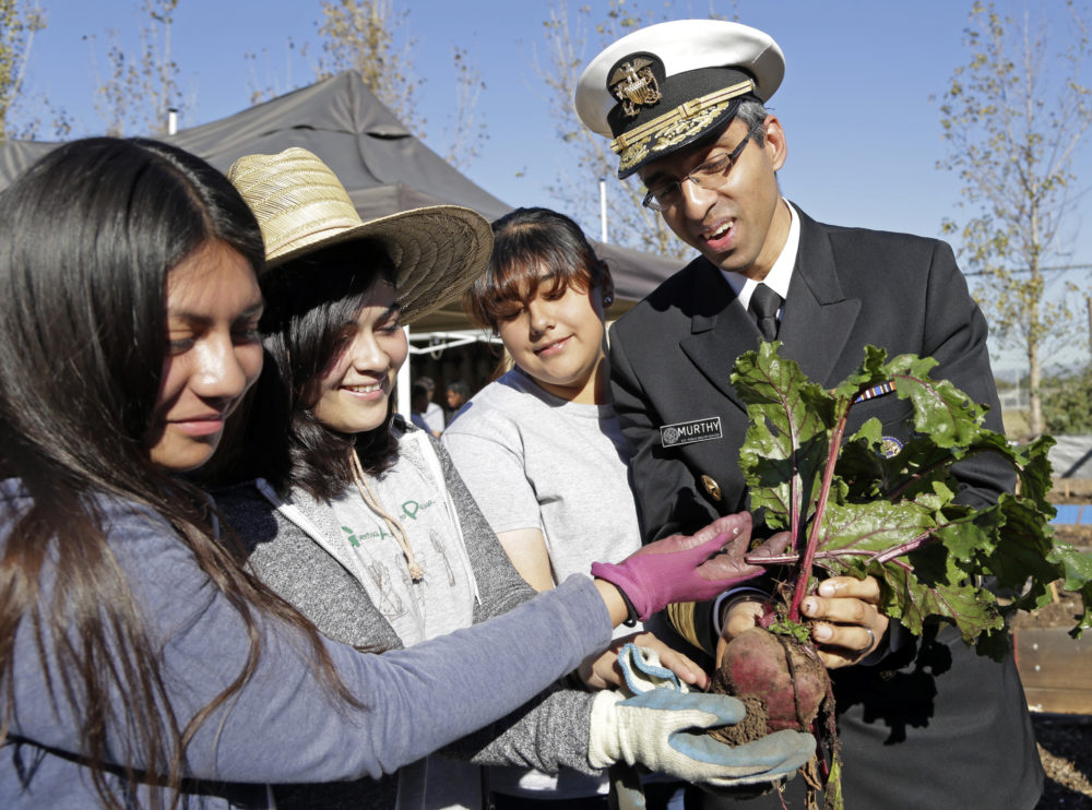 Former U.S. Surgeon General Vivek Murthy and John C. Fremont High School students hold a beet grown in the school's Gardening Apprenticeship Program plot on the campus south of downtown Los Angeles Friday, Nov. 20, 2015. (Nick Ut/AP Photo)