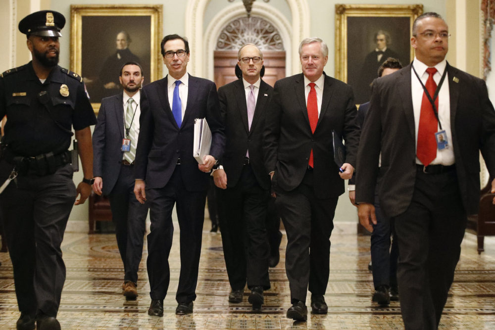 Treasury Secretary Steven Mnuchin, left, accompanied by White House Legislative Affairs Director Eric Ueland and acting White House chief of staff Mark Meadows, walks to the offices of Senate Majority Leader Mitch McConnell on Capitol Hill Tuesday, March 24, 2020. (Patrick Semansky/AP)