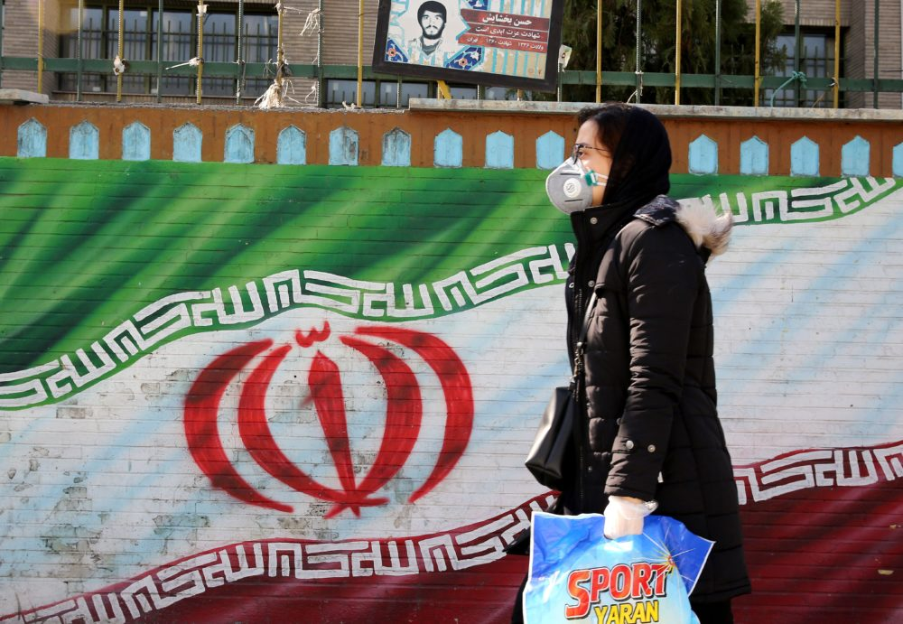 An Iranian woman wearing a mask walks past a mural displaying her national flag in Tehran. (Atta Kenare/AFP via Getty Images)