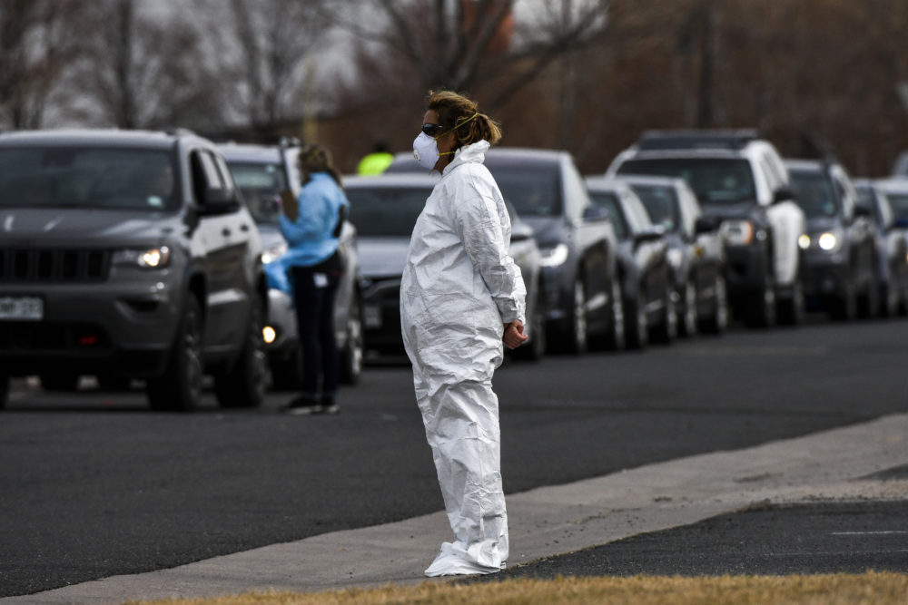 A healthcare worker watches over the line of people waiting to be tested for COVID-19 at the state's first drive-up testing center in Denver. (Michael Ciaglo/Getty Images)