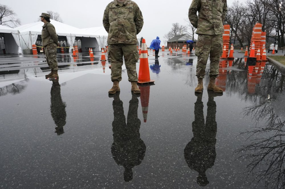 National Guard troops stand by as people wait to be tested for coronavirus at the state's first drive through mobile testing center at Glen Island Park in New Rochelle, New York on March 13. (Timothy A. Clary/AFP via Getty Images)