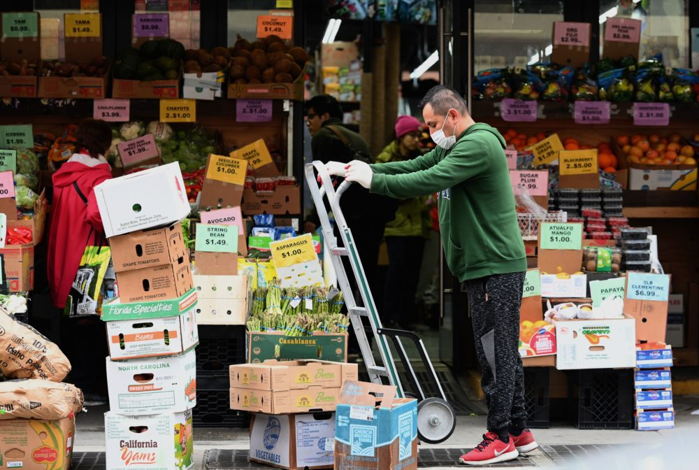 A worker stocks up on groceries at a local supermarket on March 20 in the Brooklyn, New York. (Angela Weiss/AFP/Getty Images)