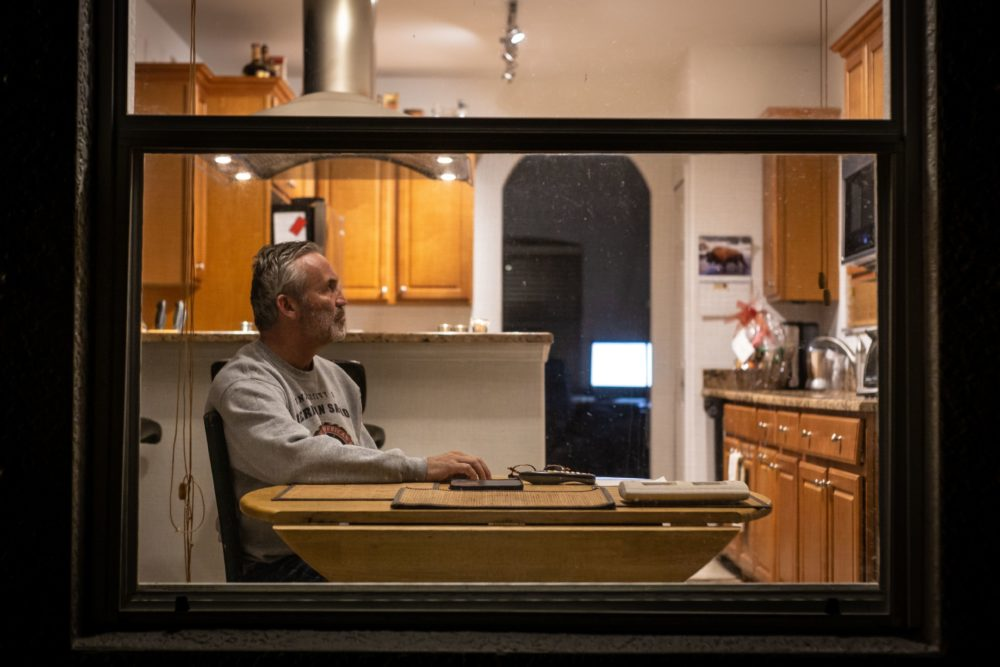 Charlie McDonald, 59,  who is suffering from the novel coronavirus (Covid-19) watches CNN in his kitchen in Naples in Naples, Florida. (ZAK BENNETT/AFP via Getty Images)