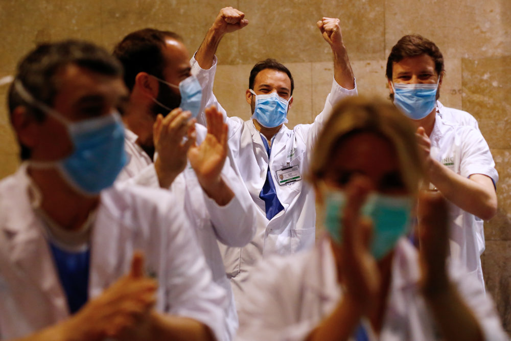 "Healthcare workers dealing with the new coronavirus crisis in Spain, applaud in return as they are cheered on by people outside ""El Clinic"" University Hospital in Barcelona on March 26, 2020.  (PAU BARRENA/AFP via Getty Images)"