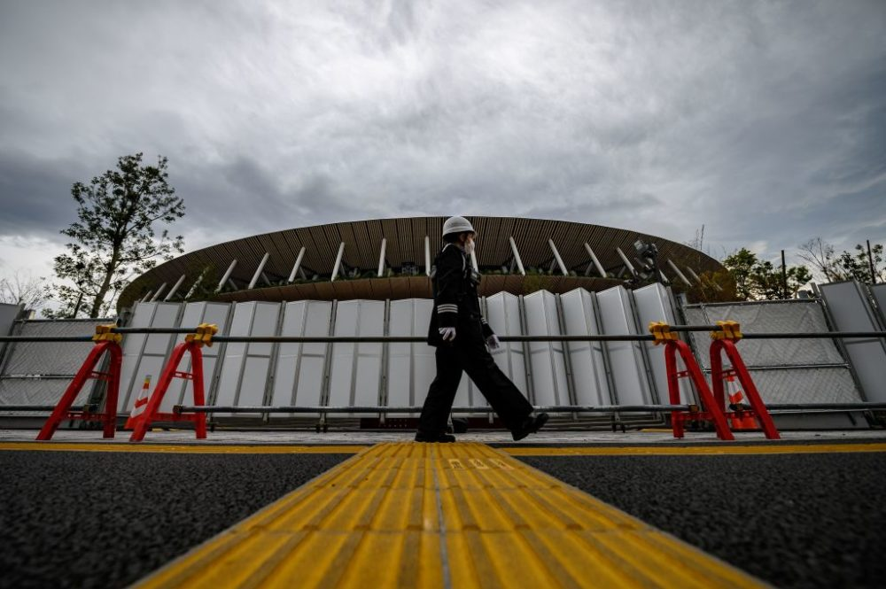 A security guard wearing a face mask walks in front of a construction site at the Japan National Stadium in Tokyo three days after the historic decision to postpone the 2020 Tokyo Olympic Games. (Philip Fong/AFP via Getty Images)