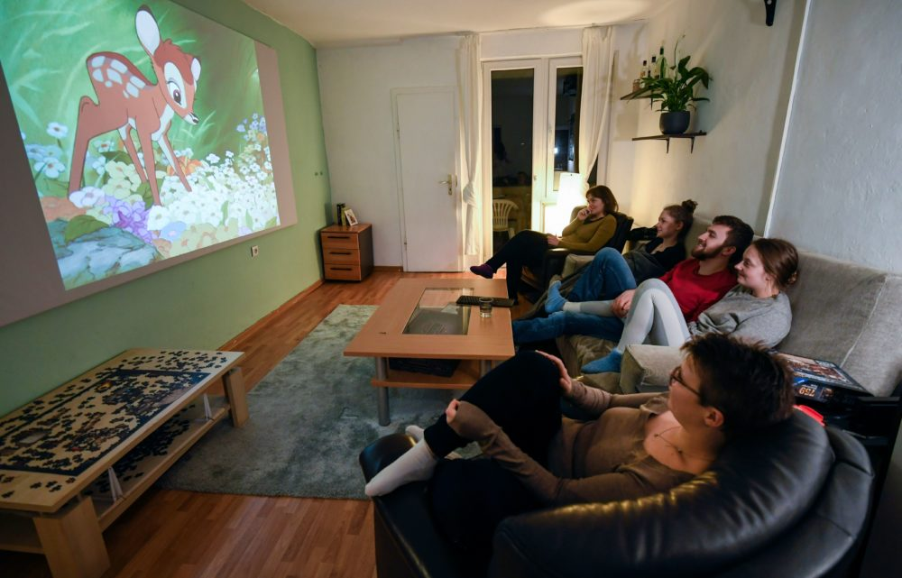 Members of a flat-sharing community watch the 'Bambi' film of Disney at their living room, in Dortmund, western Germany, on March 27, 2020, amidst the pandemic of the new coronavirus COVID-19. (INA FASSBENDER/AFP via Getty Images)