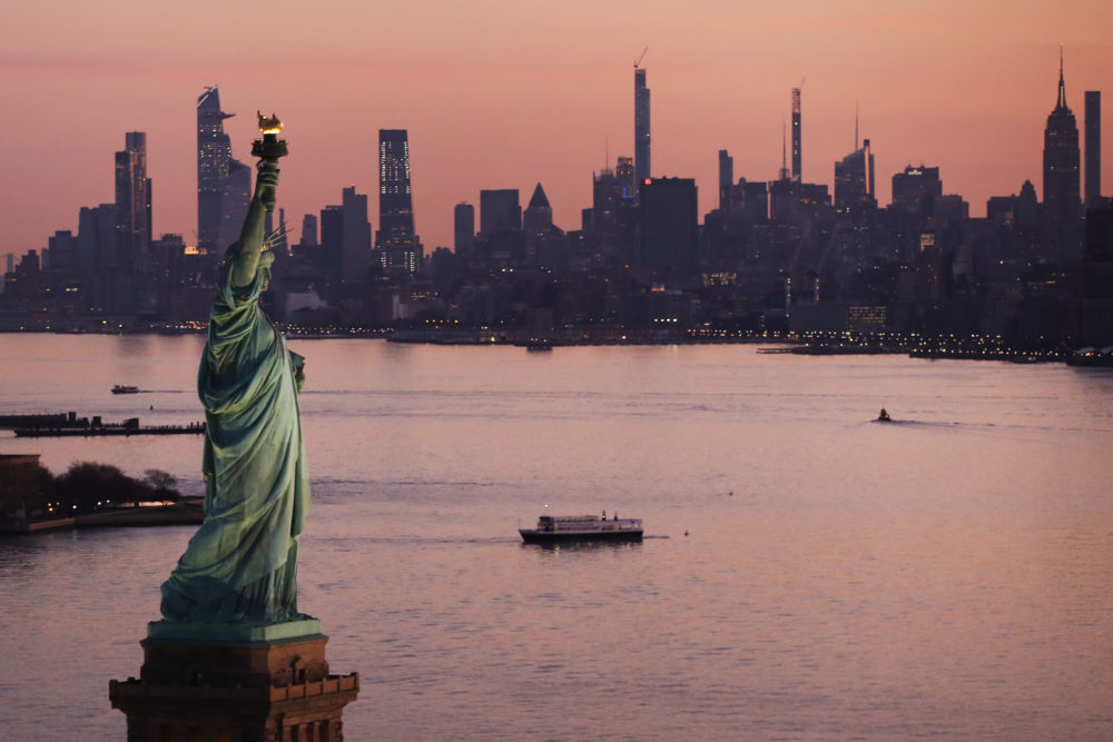 Dawn breaks over The Statue of Liberty as Manhattan and the nation struggles to contain the number of coronavirus cases on March 18, 2020 in New York City. Across the city businesses, schools and places of work have been shutting down leading to empty streets and quiet neighborhoods. (Spencer Platt/Getty Images)
