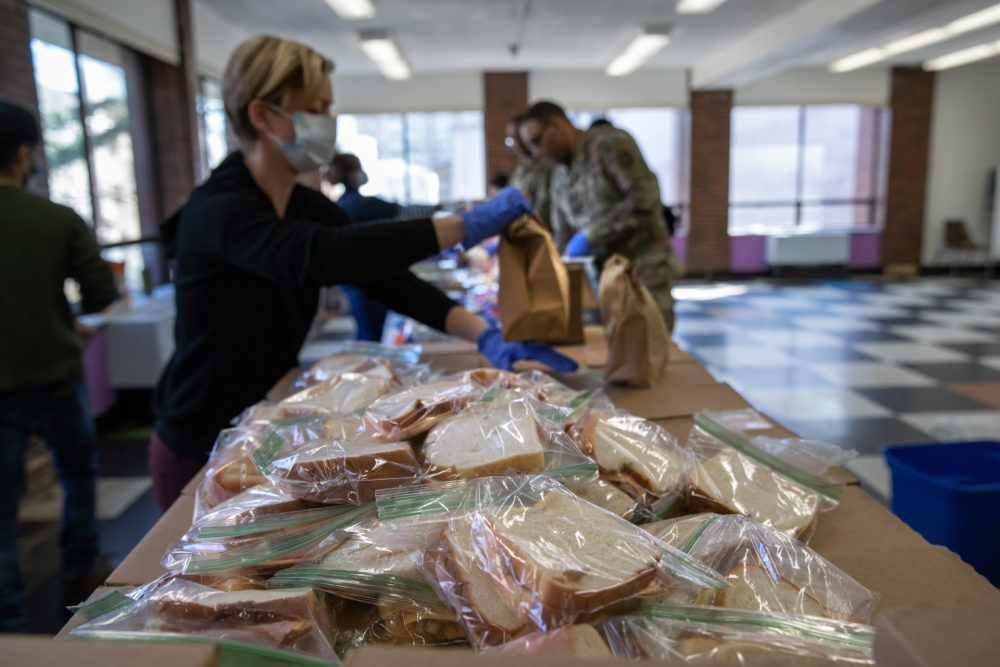 Volunteer Rhiannon Navin and U.S. National Guard troops put together meals for distribution to local residents at the WestCop community center on March 18, 2020 in New Rochelle, New York. New Rochelle has been a hot spot for the COVID-19 pandemic in the U.S. (John Moore/Getty Images)