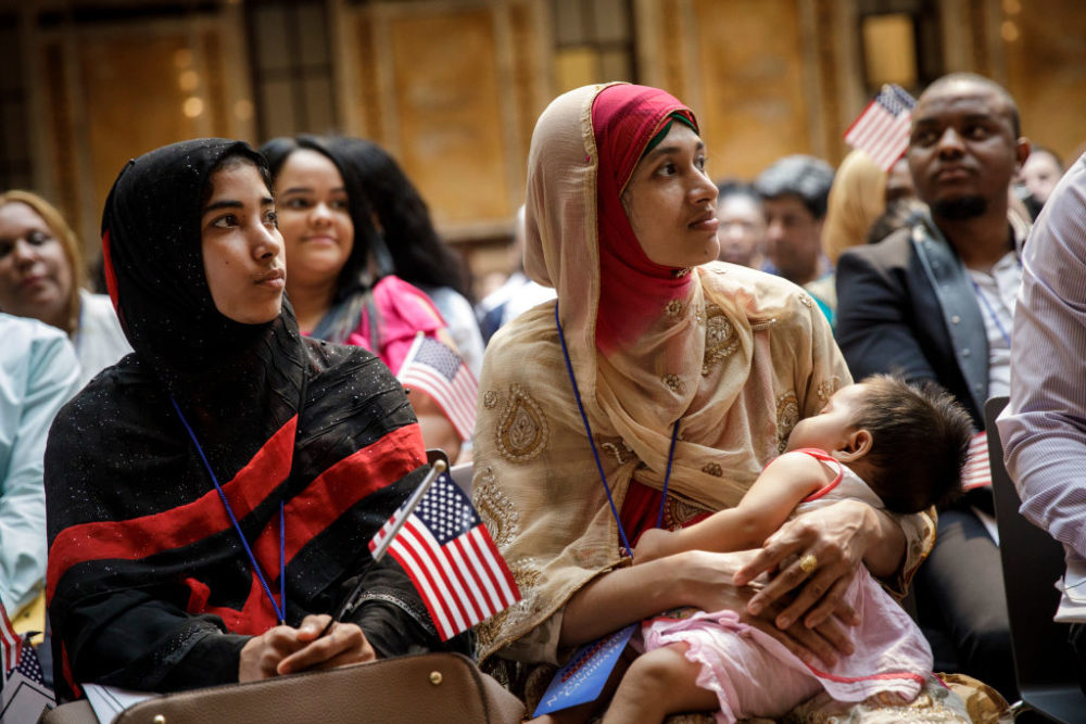 Mosammat Rasheda Akter, originally from Bangladesh, holds her 7 month-old daughter Fahmida as she waits to officially become a U.S. Citizen during a naturalization ceremony at the New York Public Library, July 3, 2018 in New York City. (Drew Angerer/Getty Images)