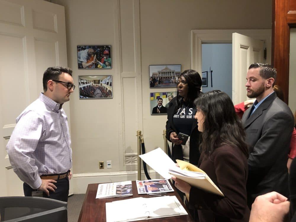 Prisoner rights activists present a letter to a staffer in Gov. Charlie Baker's office. (Deborah Becker/WBUR)
