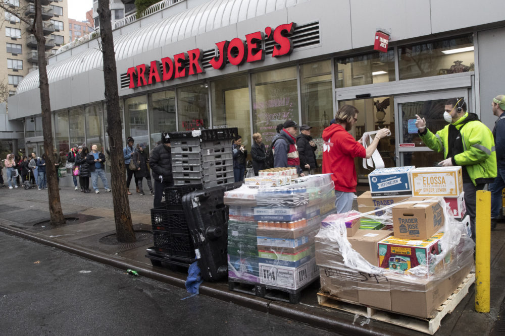 A Trader Joe's employee, second from right, receives groceries from a delivery man, right, as customers line up to enter the store, Friday. (Mary Altaffer/AP)