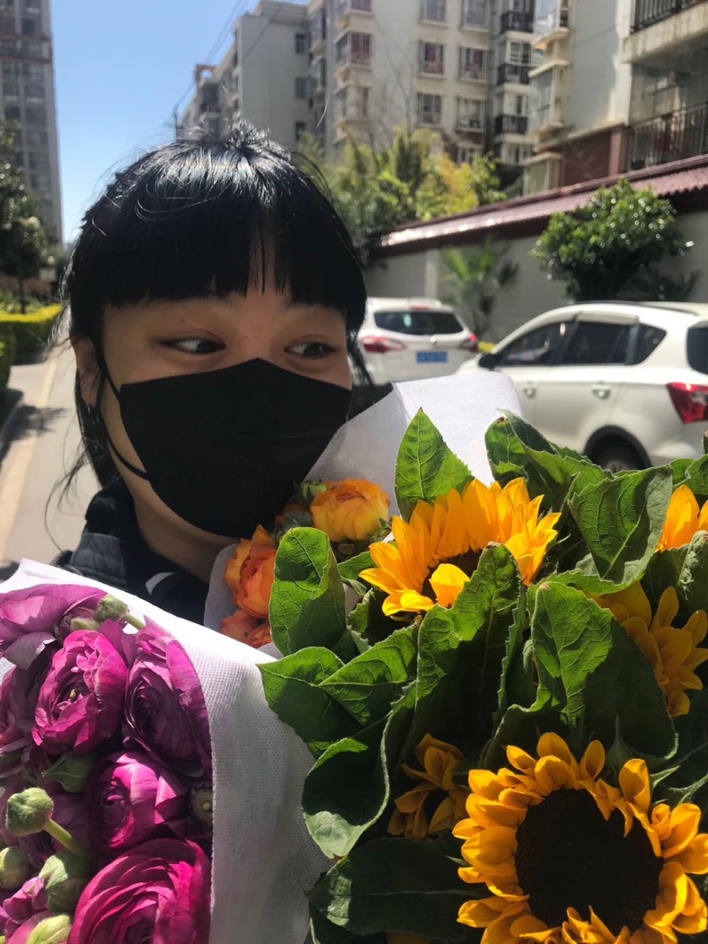 The author on March 1 with three bouquets of flowers from the wet market near her mother's apartment in Kunming, China.  (Courtesy)