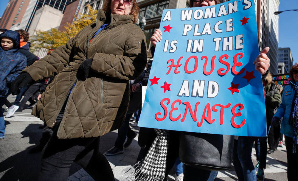 A woman holds a sign during a rally and march on October 13, 2018 in Chicago. (Kamil Krzaczynski/AFP/Getty Images)