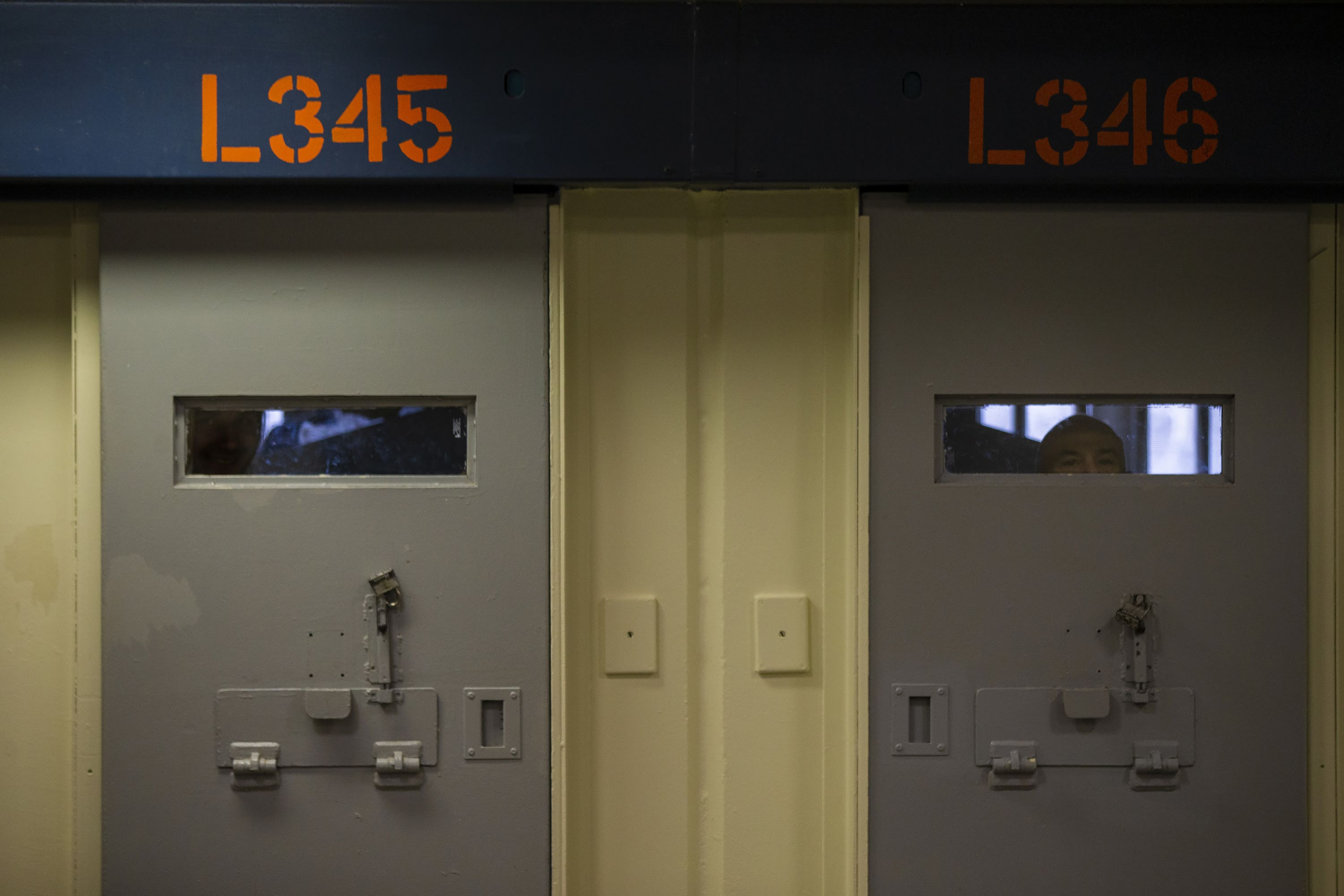 Inmates peer through the windows behind cell doors inside the Worcester County jail.(Jesse Costa/WBUR)