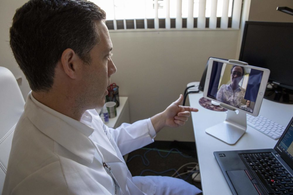 "The coronavirus pandemic has prompted more people in Massachusetts to turn to telemedicine. Here, Dr. Philip Ciampa from the Atrius Health innovation center (left) talks with a colleague (at the top of the screen), in a demonstration of a ""virtual visit."" (Robin Lubbock/WBUR)"