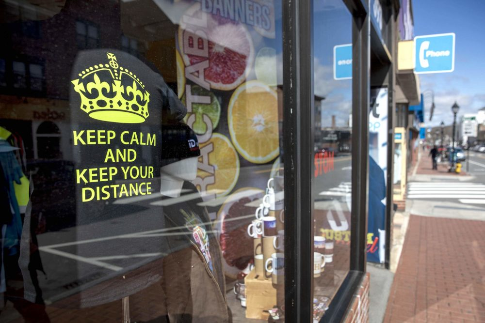 """A T-shirt in the window of the iD art GraphicsShop on Moody Street, Waltham, says """"Keep Calm And Keep Your Distance."""" (Robin Lubbock/WBUR)"""