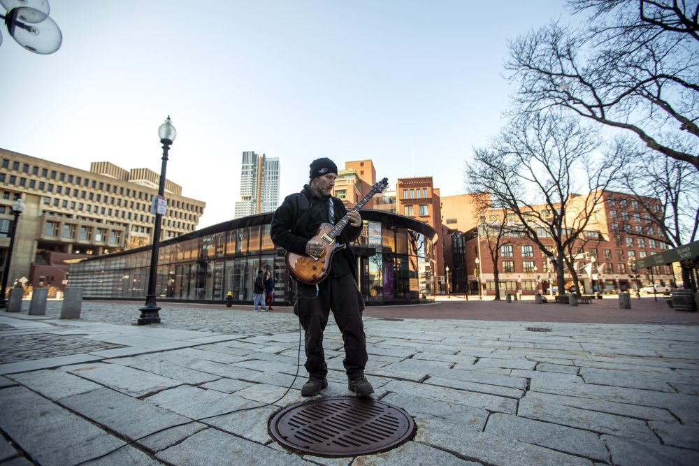 Street guitarist Matty X plays to an empty Faneuil Hall in late March. Faneuil Hall retailers have been pushing for a reprieve on April rent after last month's shuttering of non-essential businesses amid the coronavirus pandemic. (Jesse Costa/WBUR)