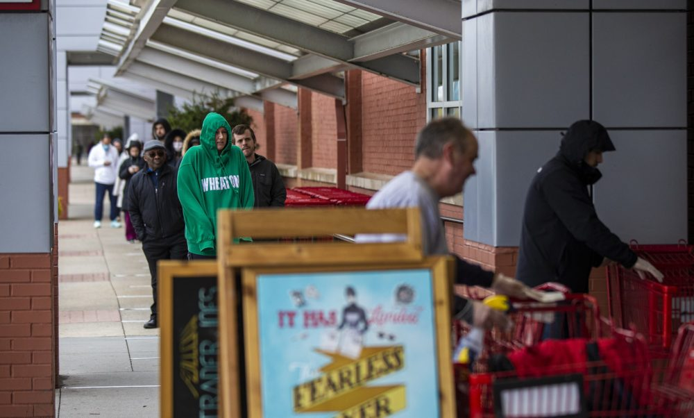 A long line of people wait to gain entrance into Trader Joe's in Assembly Square, March 30. (Jesse Costa/WBUR)