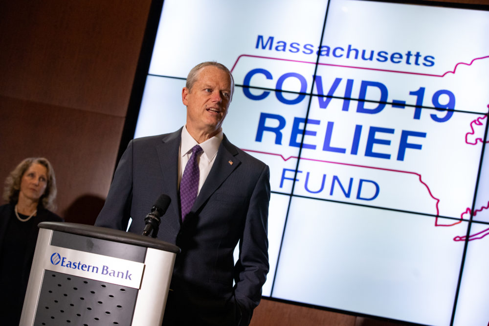 Gov. Charlie Baker, with First Lady Lauren Baker behind him, announces the formation of statewide COVID-19 relief fund. (Sam Doran/State House News Service)