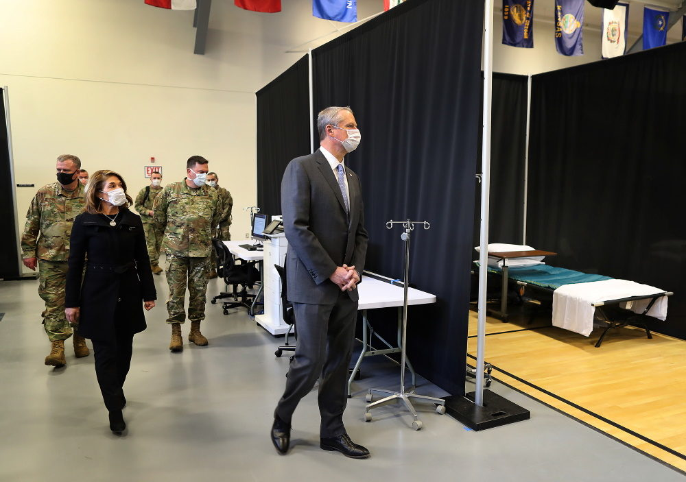 Gov. Charlie Baker and Lt. Gov. Karyn Polito joined the Massachusetts National Guard and Michael Lauf, President and CEO of Cape Cod Healthcare as they toured a field medical station in a gymnasium at Joint Base Cape Cod. (John Tlumacki/Boston Globe via SHNS)
