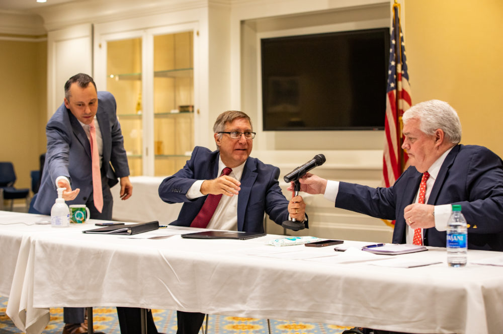 State Rep. Aaron Michlewitz, state Sen. Michael Rodrigues, and Administration and Finance Secretary Michael Heffernan sanitized their hands while passing around a microphone during Tuesday's economic roundtable. (Sam Doran/SHNS)