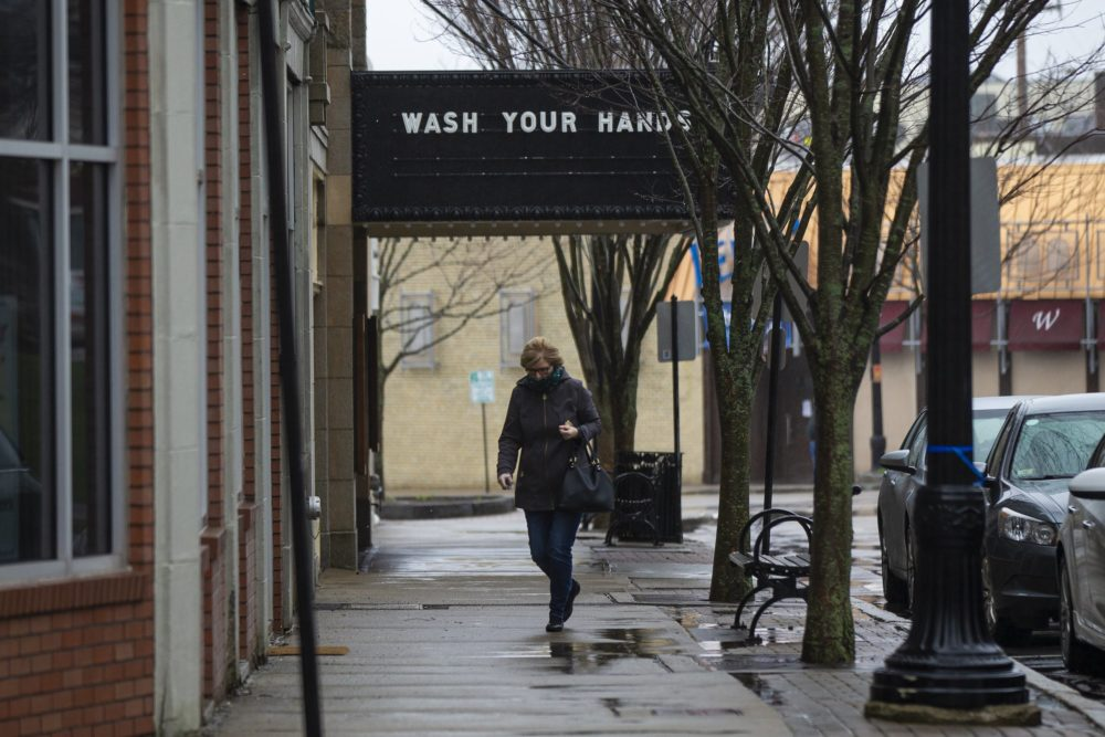 "A woman walks past a closed Norwood Cinema where the marquee reads ""Wash your hands."" (Jesse Costa/WBUR)"