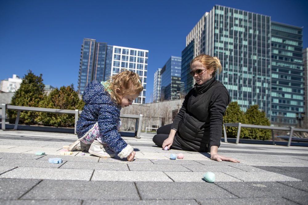 Two-year-old Thayer Elia and her mother Alaska draw with chalk on the ground at the Seaport Common. (Jesse Costa/WBUR)