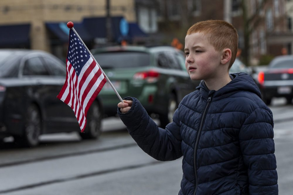 A young boy pays his respects to Mary Foley, waving a flag as her funeral procession passes. (Jesse Costa/WBUR)