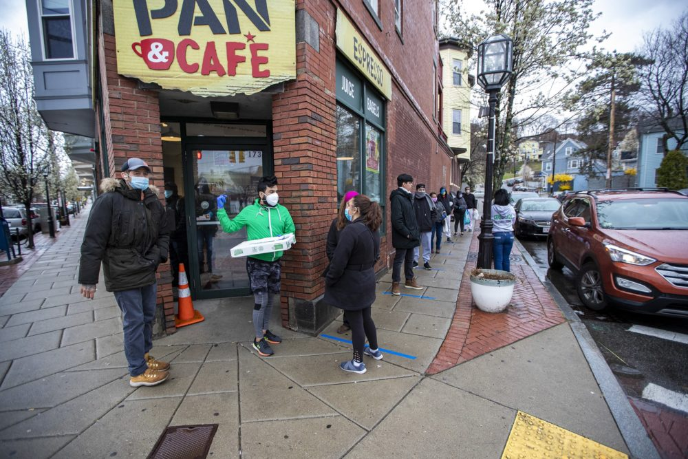 A line of Chelsea residents extends down Forsyth Street to place orders for food being distributed by the Chelsea Collaborative. (Jesse Costa/WBUR)
