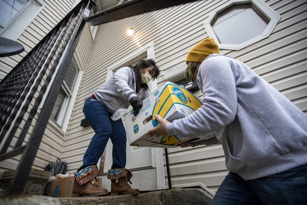 Reymer Pineda hands a box of donated food to Gladys Vega to leave on the front porch of the house. All members of the household have contracted COVID-19, and will come out after Vega calls them to let them know. (Jesse Costa/WBUR)