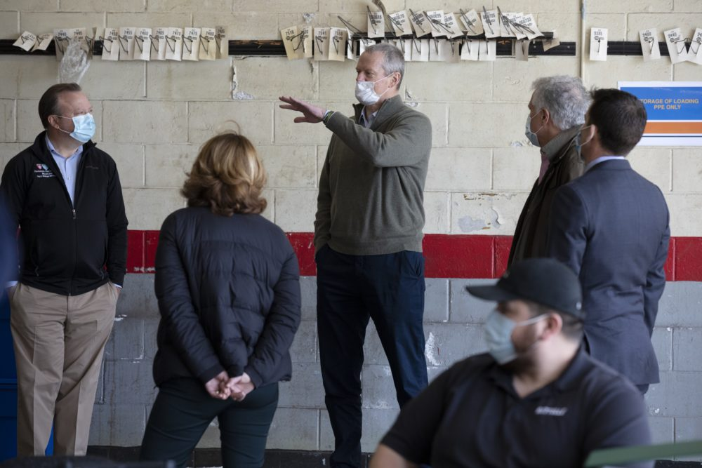 Massachusetts Gov. Charlie Baker (center) wears a protective mask while visiting the Battelle N95 decontamination site, on Saturday, April 11, in Somerville, Mass. (Michael Dwyer/AP)
