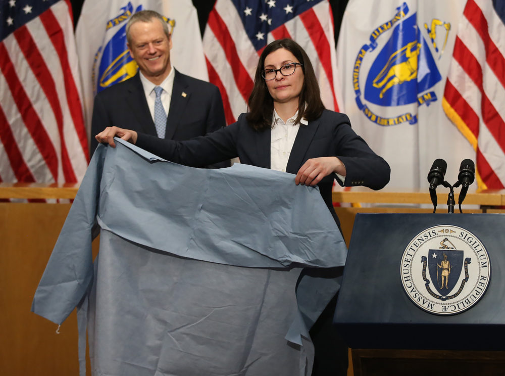 Gov. Charlie Baker looks on as Brenna Schneider, CEO of 99Degrees, shows off a surgical isolation gown during a media availability at the State House to discuss updates relating to COVID-19 on April 13, 2020. (Nancy Lane/MediaNews Group/Boston Herald)