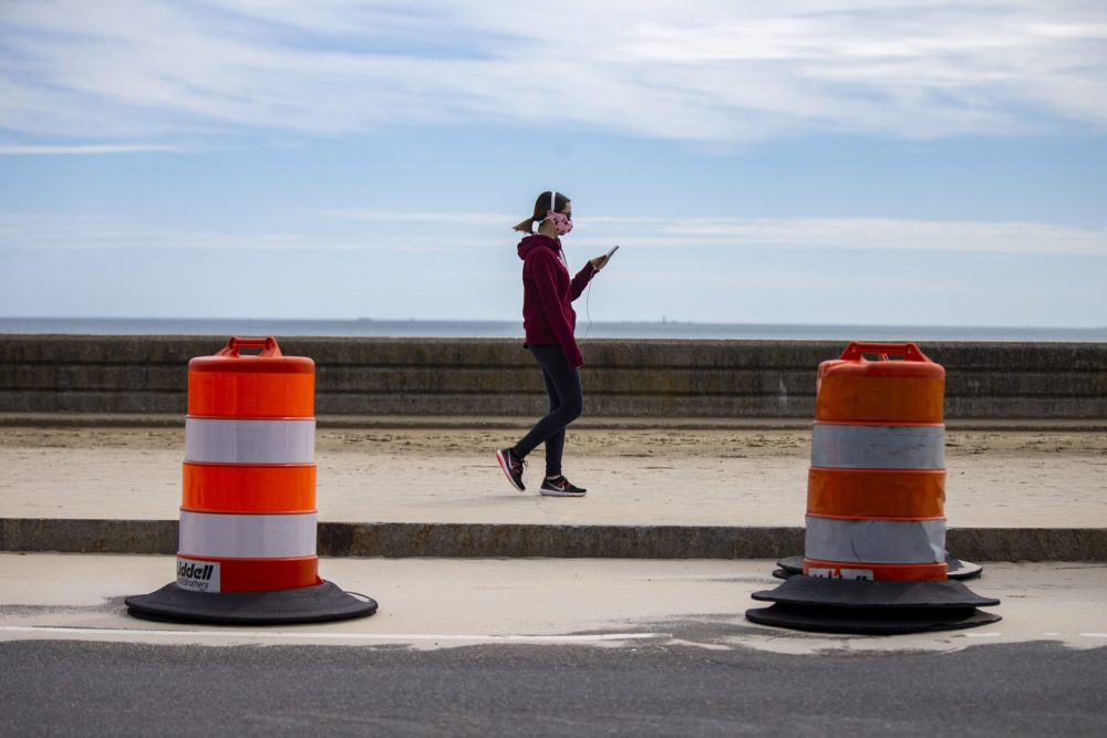 A woman looks at her phone while walking along Revere Beach. (Jesse Costa/WBUR)