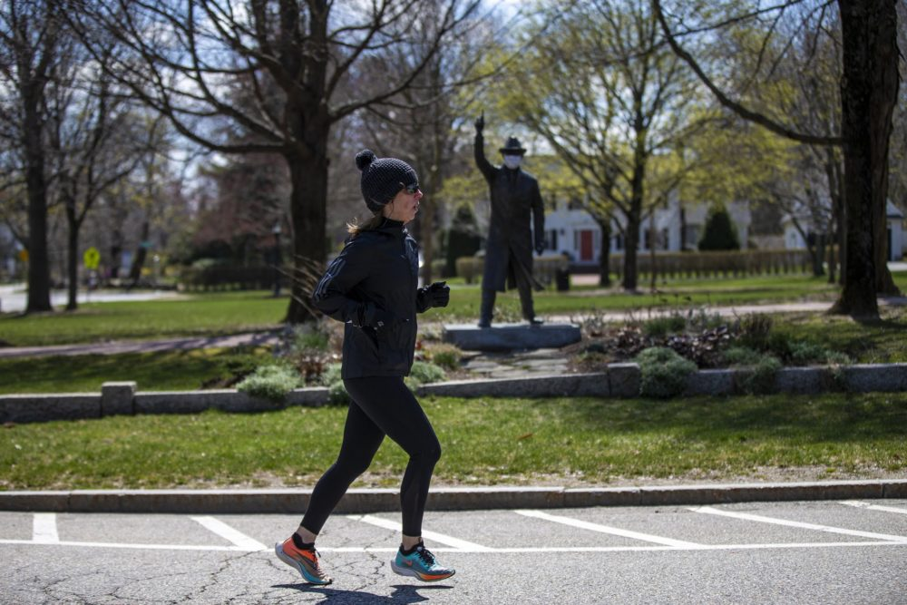 "As she performs a virtual half-marathon to keep up her training for September, Hopkinton resident Joy Donohue runs past ""The Starter"" statue in the town's common -- the site of the start of the Boston Marathon. (Jesse Costa/WBUR)"