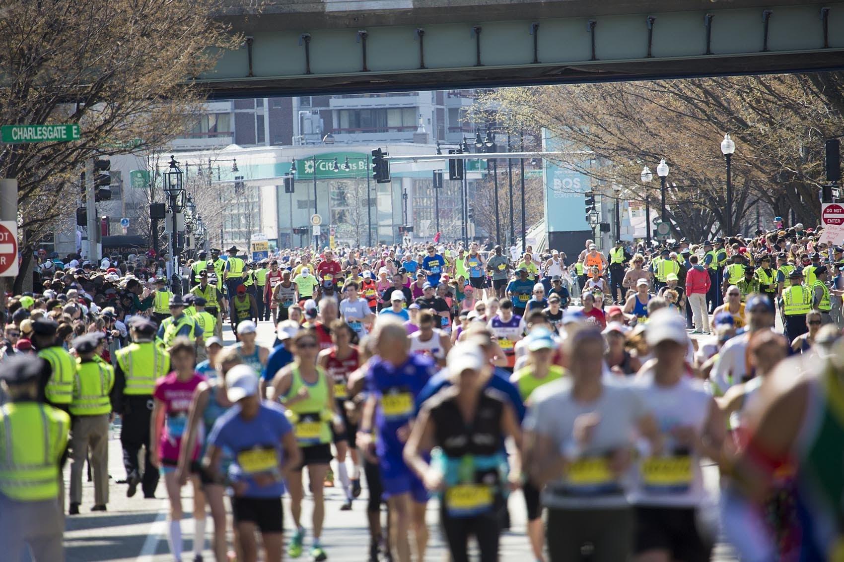 Hundreds of runners pour through Kenmore Square at the 2016 Boston Marathon. (Jesse Costa/WBUR)