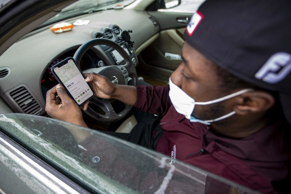 In his car at Costco in Dedham, Instacart shopper Shamar Martin looks at a double order on the Instacart app. (Jesse Costa/WBUR)