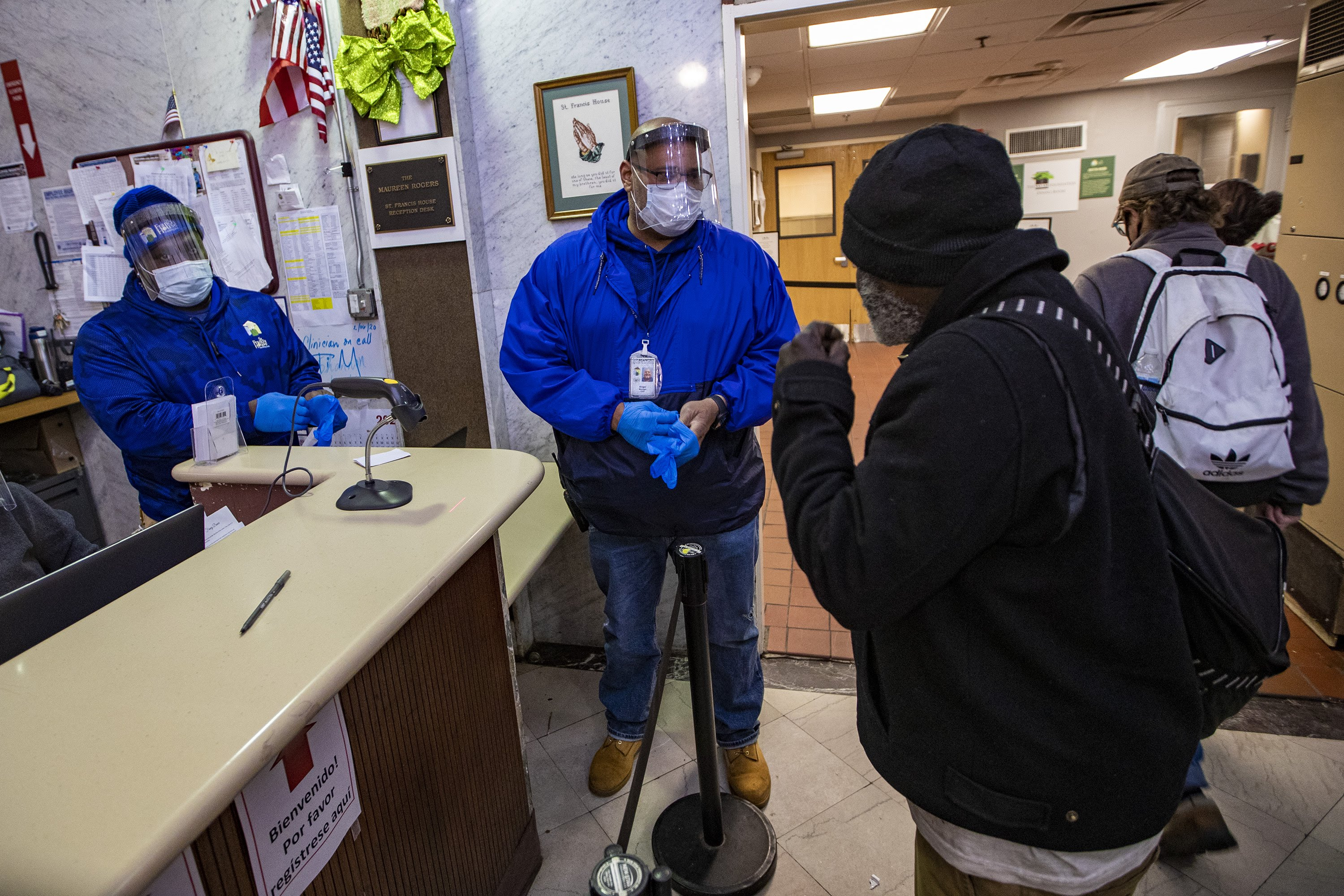 Angel Marte puts on a pair of nitrile gloves before working on some paperwork for a guest entering St. Francis House in Boston. (Jesse Costa/WBUR)