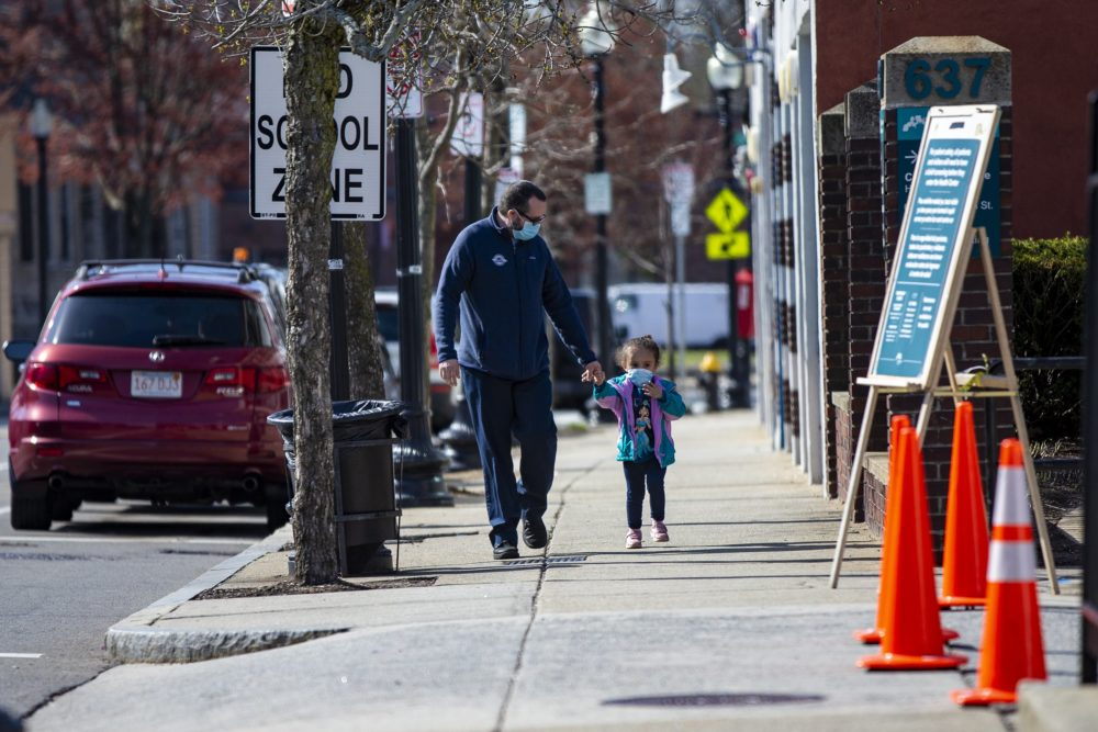 A father and his young daughter walk down Washington Street on their way to Codman Square Health Center. (Jesse Costa/WBUR)