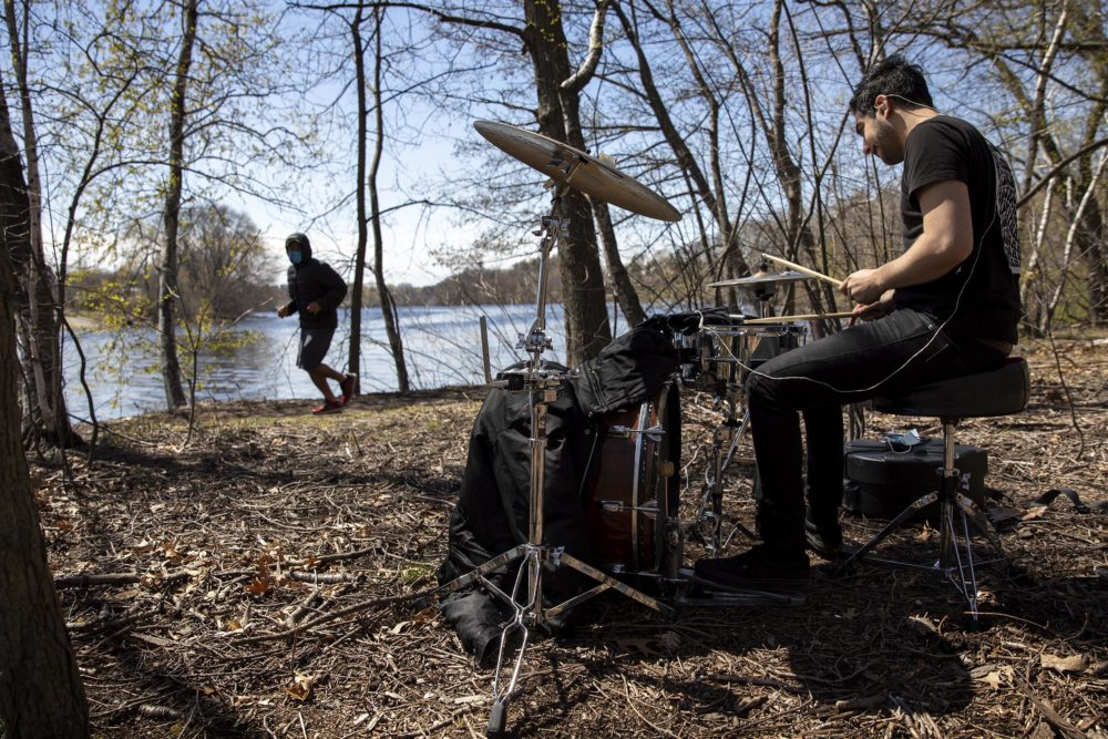 A runner along the Charles River sees Sander Bryce drumming in the woods. (Robin Lubbock/WBUR)