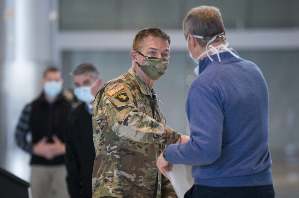 """Gov. Charlie Baker and U.S. Army Chief of Staff General James C. McConville elbow """"bump"""" after their press conference in the Boston Convention & Exhibition Center on April 18, 2020. (Blake Nissen/The Boston Globe)"""
