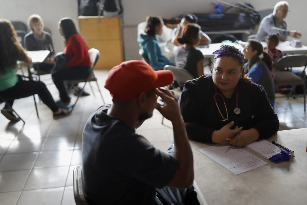 In this Dec. 14, 2019, photo, Dr. Psyche Calderon, right, works with a patient in a shelter for migrants in Tijuana, Mexico. (Gregory Bull/AP)